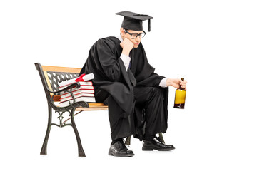 Sad college graduate drinking alcohol seated on bench
