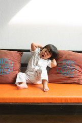 Cute little girl stretching in sofa.