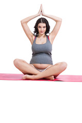 Pregnant woman practising yoga and meditating