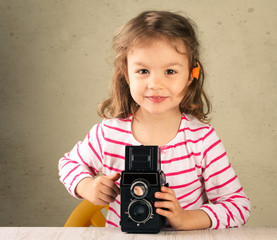 Little girl taking pictures with a vintage film camera.