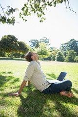 Stylish relaxed man using his laptop in the park