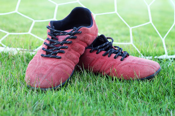 Red shoes green grass in a stadium.