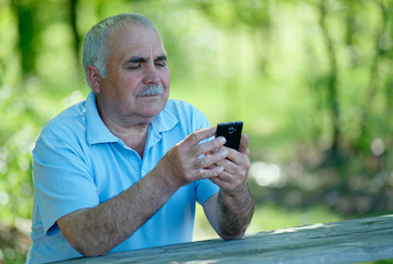 Senior man reading a text message on his phone
