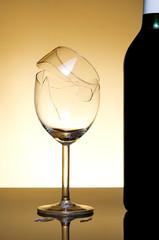Vine bottle and broken glass on orange background