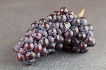 Blue grape cluster on slate board