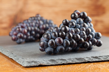 Blue grape clusters on slate board