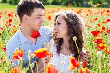 Young happy couple on a meadow full of poppies