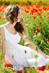 Young beautiful girl in the field of poppies