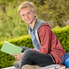 Student boy holding book sitting outside school