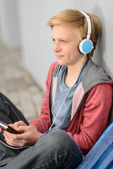 Thoughtful teenage student listening to music