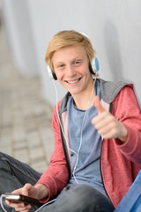 Happy teenage student thumb-up listen to music