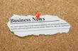Business News Headline pinned to a cork notice board