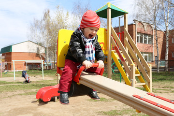 happy baby on seesaw outdoors