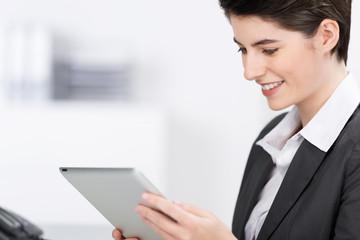 lächelnde geschäftsfrau liest am tablet