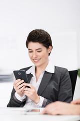 frau schaut auf ihr smartphone während einer besprechung