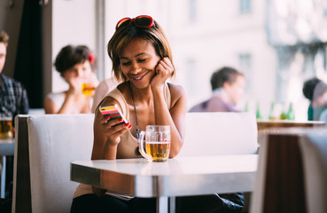 Young black woman texting and drinking beer in bar
