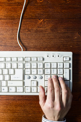 Woman hand typing on a white keyboard on wooden background