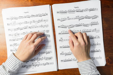 Female hands sight reading sheet music on wooden background