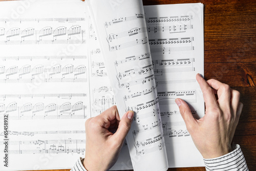 Female hands sight reading sheet music on wooden background - 65458932