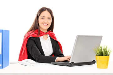 Woman in superhero costume working on laptop