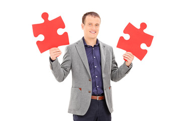 Young man holding two pieces of puzzle