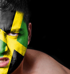 Portrait of angry man with painted flag of Jamaica