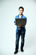 asian man standing with laptop on gray background