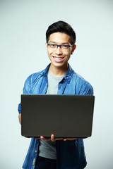 Young smiling asian man standing with laptop on gray background