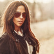 Outdoor fashion portrait of young pretty woman in sunglasses