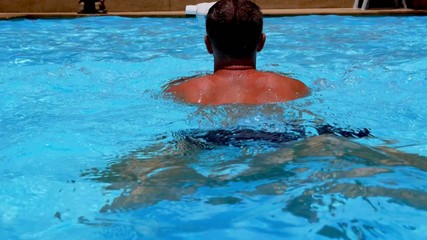 Young Tanned Muscular Man Swimming in Blue Pool in Slow Motion.