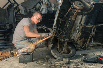 Young mechanical worker repairing an old vintage car body