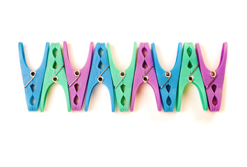 Row of plastic clothes pegs on a white background