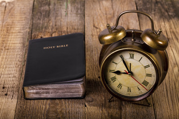 Bible with clock on wood