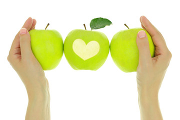 Hands with a row of green apples and heart