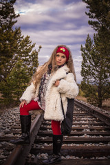 Girl 8 years in the white fur coat standing on the rails
