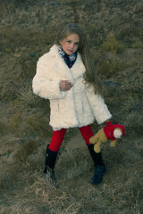 Girl 8 years in the white fur coat in red tights