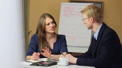 Young attractive female office worker with man on work meeting