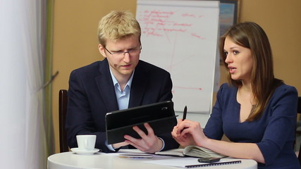 Office meeting man shows charts device, woman writes down