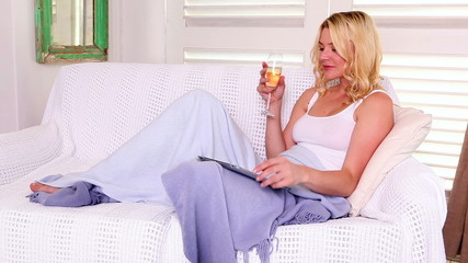 Pretty blonde relaxing on sofa with tablet and wine