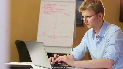 Laptop typing businessman writing making notes, financial index
