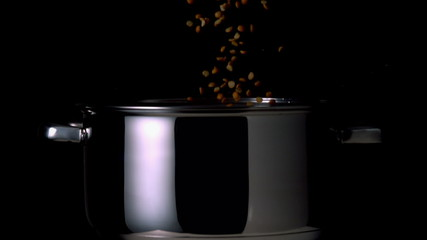 Popcorn kernels falling into pot on black background
