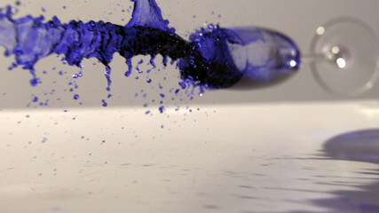 Glass of blue ink falling and spilling