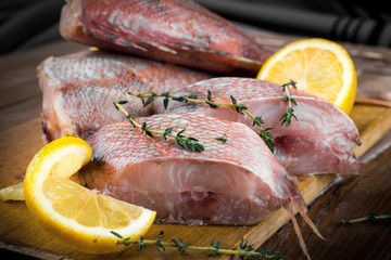 Sea bass with lemon on wooden board