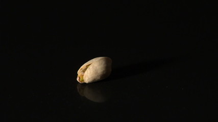 Pistachio nut spinning on black surface