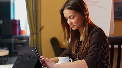 Young businesswoman at work, typing message drinking cup coffee