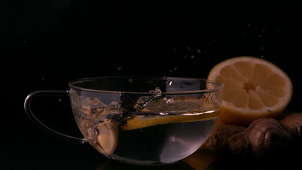 Lemon slices falling into glass cup of water