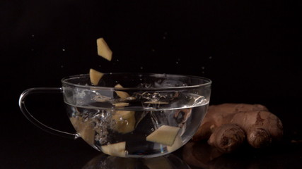 Ginger slices falling into glass cup of water