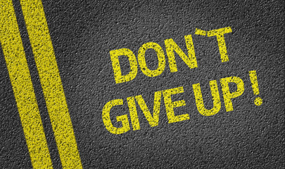 Don't Give Up written on the road