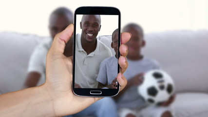 Hand showing people watching football clips on smartphone