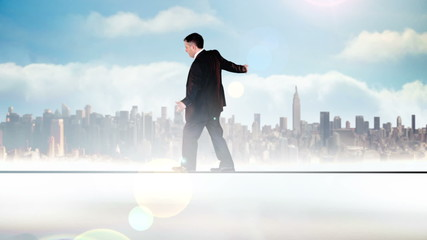 Businessman walking across tightrope with business text